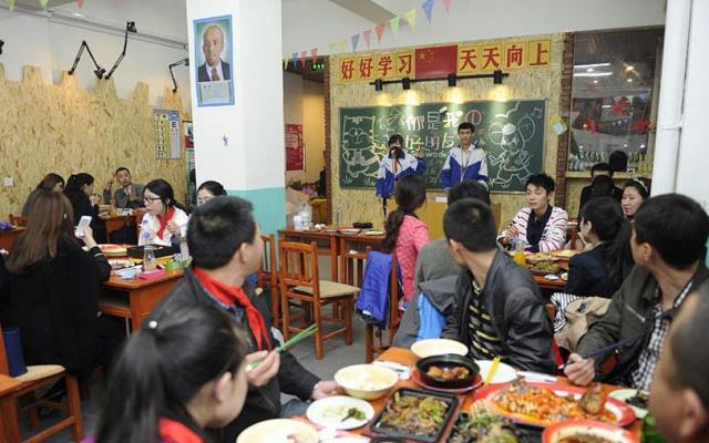Restaurace je rozvržena jako velká učebna s lavicemi, tabulí a katedrou